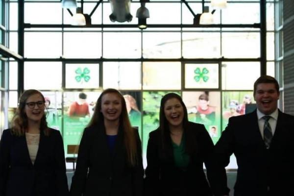 4 teens standing in front of posters with green and clovers. Left to right: three girls and a boy, all wearing business professional clothes.