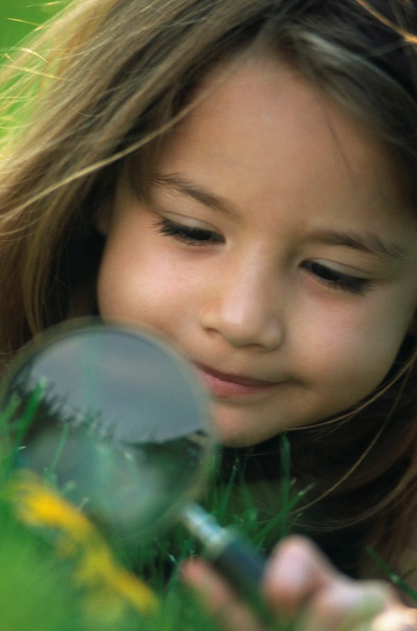 Image of girl examining plants with magnifying glass