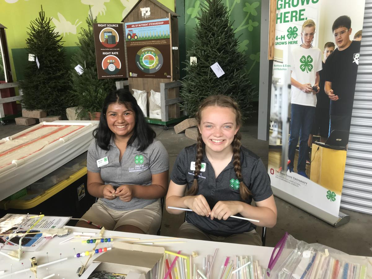 three youth members sitting behind table assisting at the Ohio State Fair