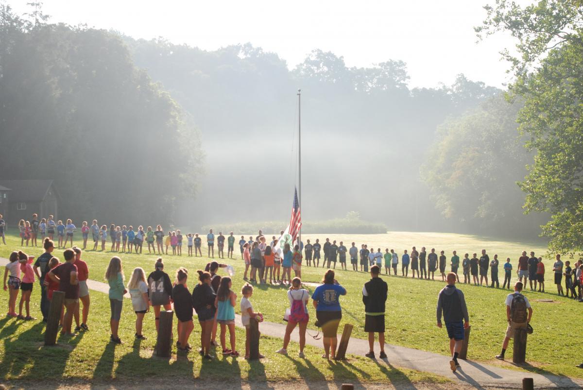 whole camp group around flag pole for morning flag raising