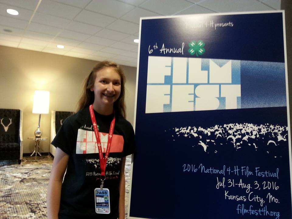 Emmy Beck-Aden with a sign advertising the 2016 FilmFest 4-H.