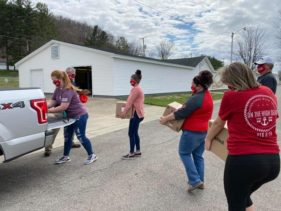 Volunteers load boxed meals into a truck.