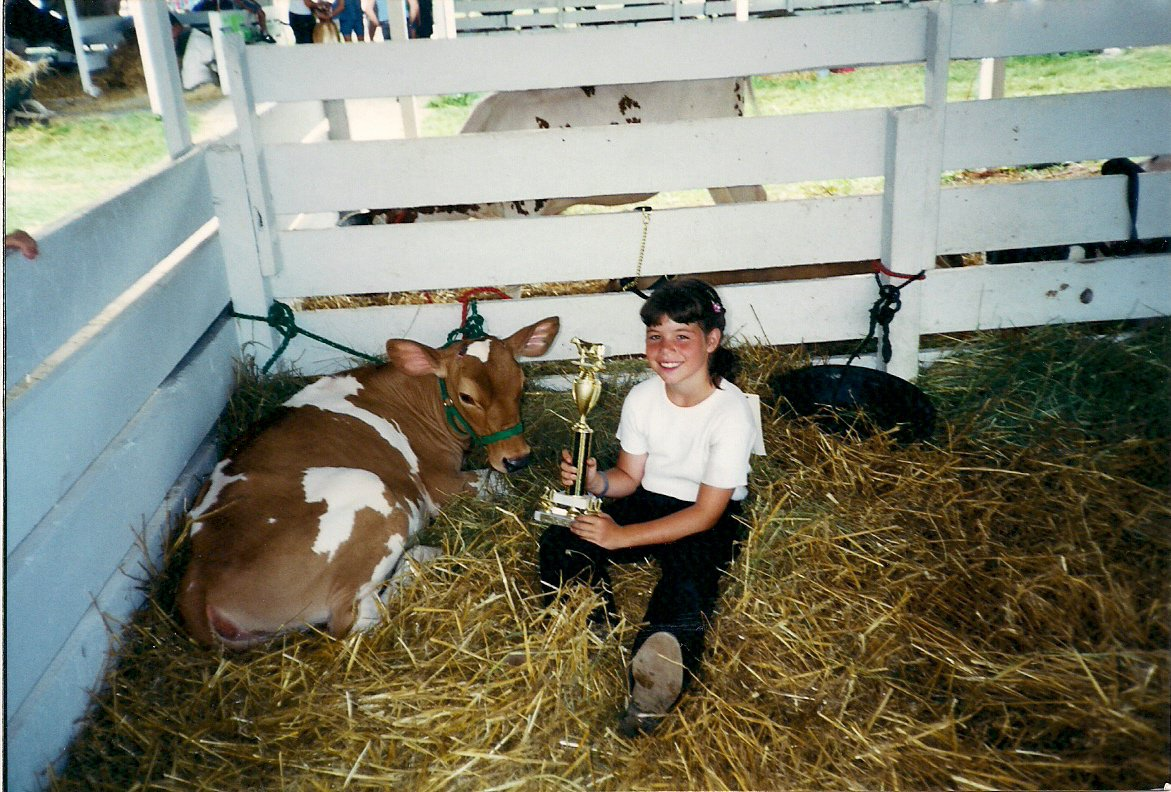 A young girl holds a trophy, sitting next to a Guernsey calf.