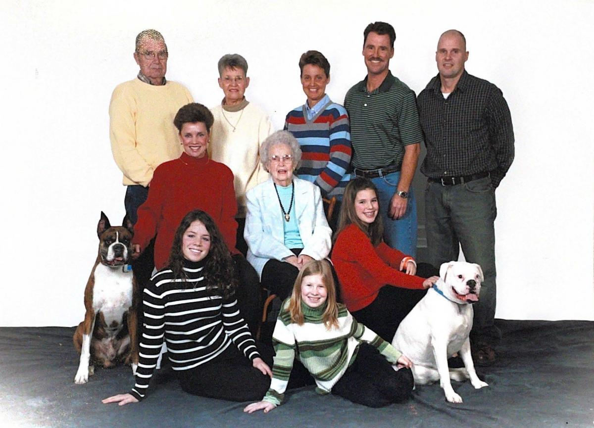 Family photo, 3 rows of people. Back: man, woman, woman, man, man. Middle: woman, woman young girl. Front: dog, young girl, young girl, dog.