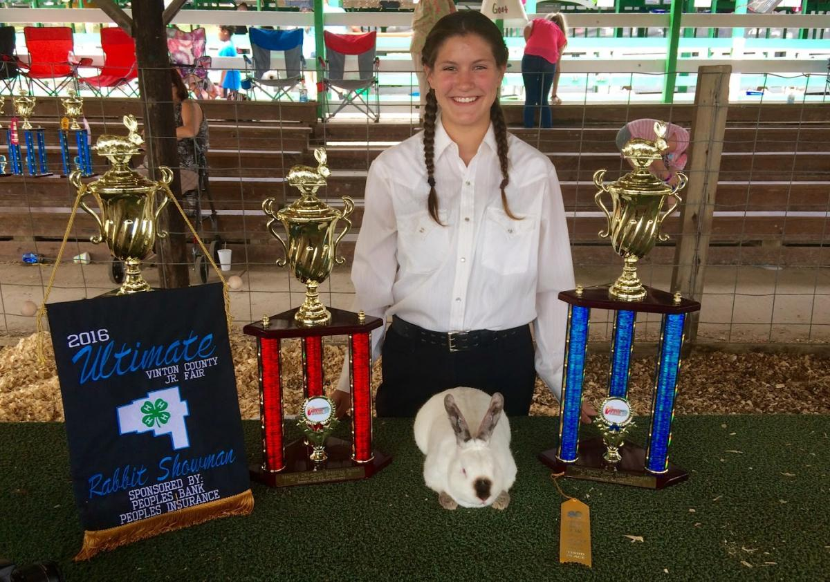 Maddie, in front of her on a table is a rabbit. To the right of the rabbit is a trophy, to the left is two trophies, hanging on one trophy is a banner.