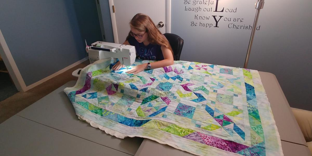 Allie Carter stitching her quilt.