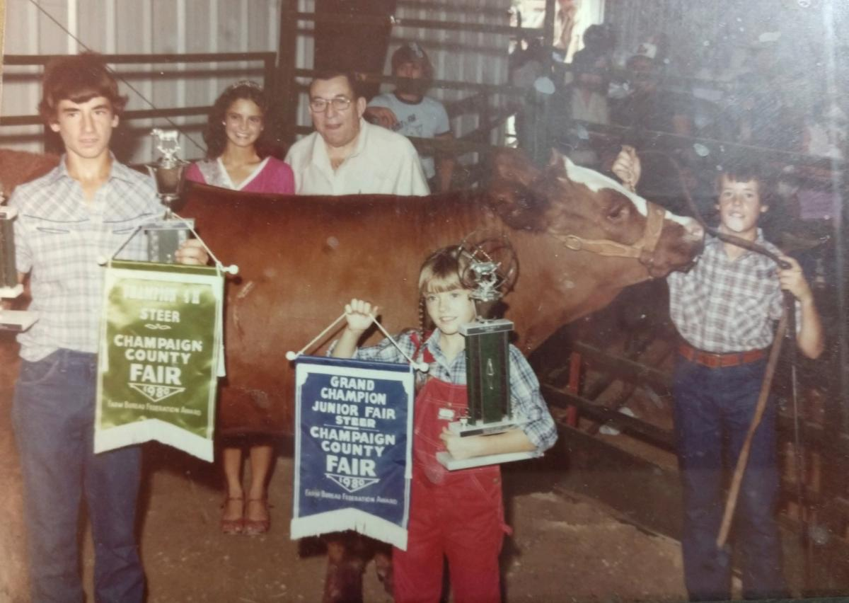 Bill holding a steer's halter. His family is around the steer holding banners and trophies.
