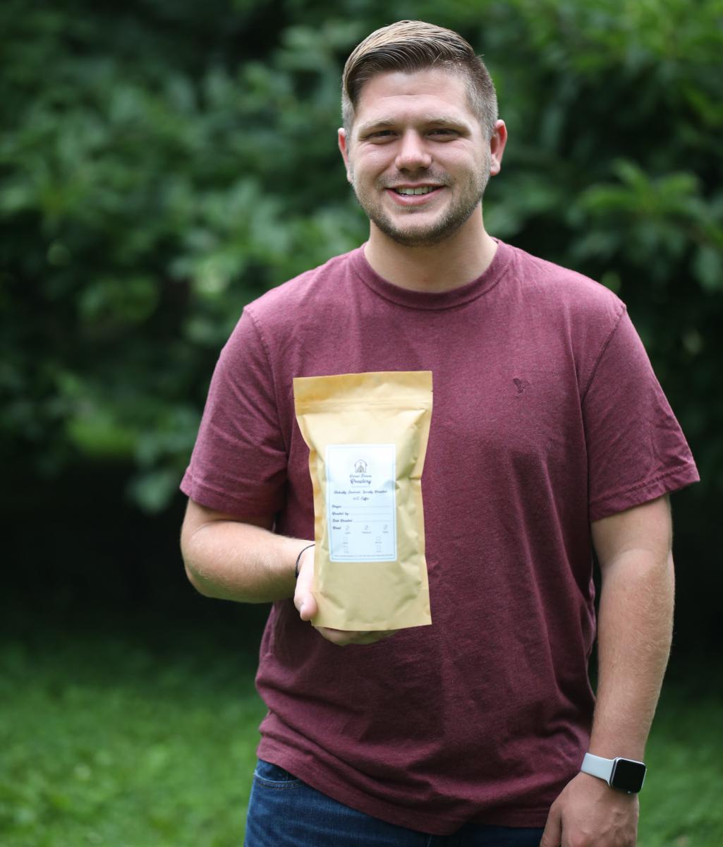 Kameron holding a bag of coffee.