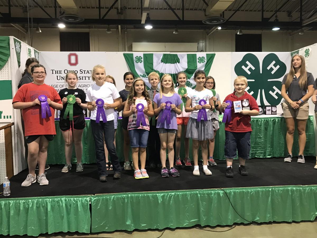 A group of 4-H members holding purple Outstanding of the Day ribbons.