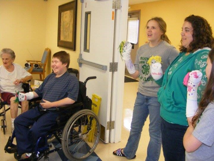 Emily is seen with other club members leading songs and making sock puppets with nursing home residents.