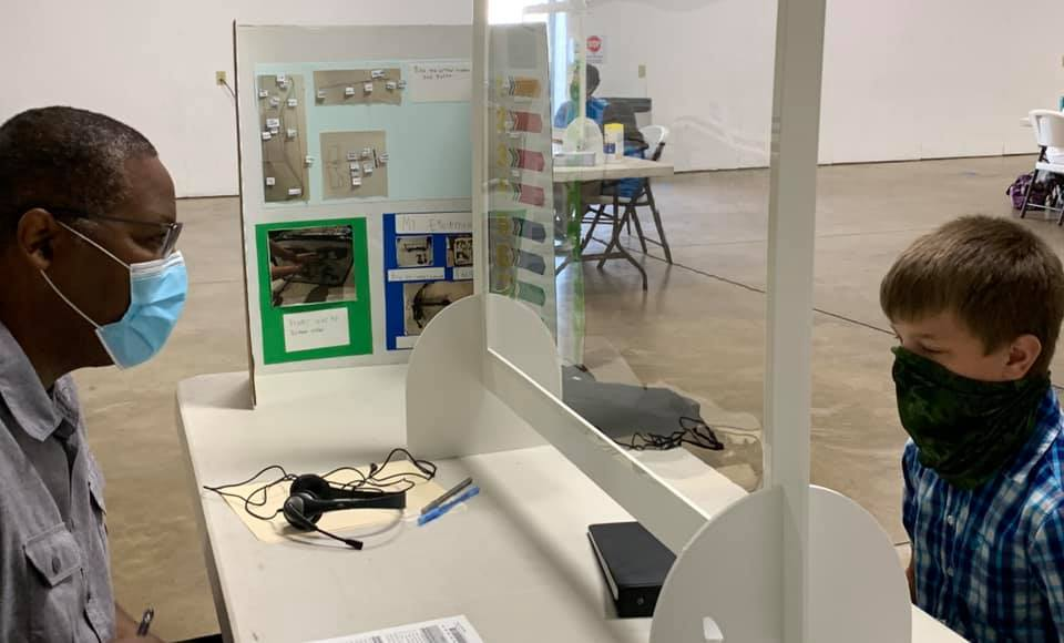 4-H project judging with masks and separated by plexiglass.