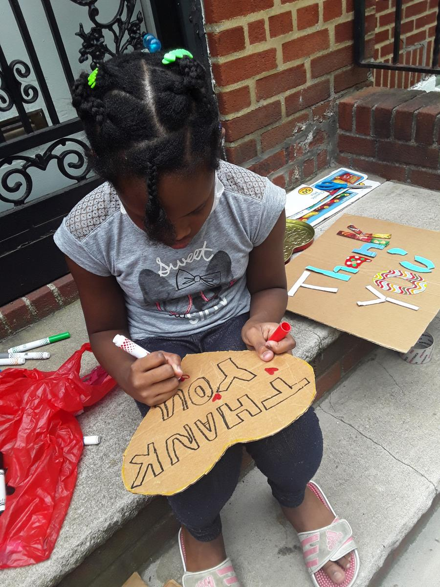Young girl making thank you cards for camp supporters.