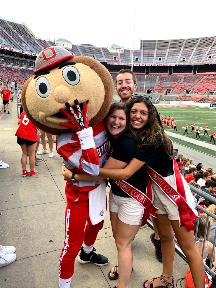 Maddie, with two other homecoming court member, hugging Brutus Buckeye in Ohio Stadium.