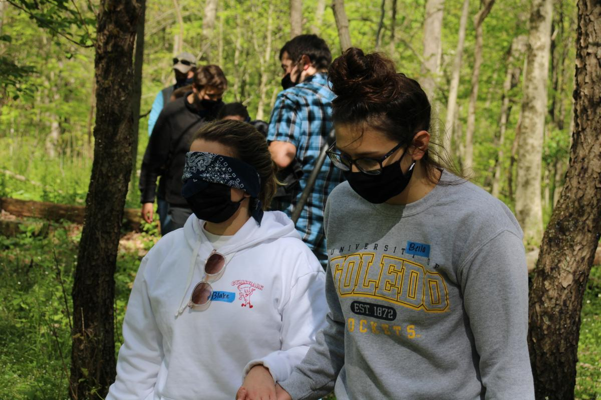 One girl guiding another blind-folded girl through a trust and communication exercise.