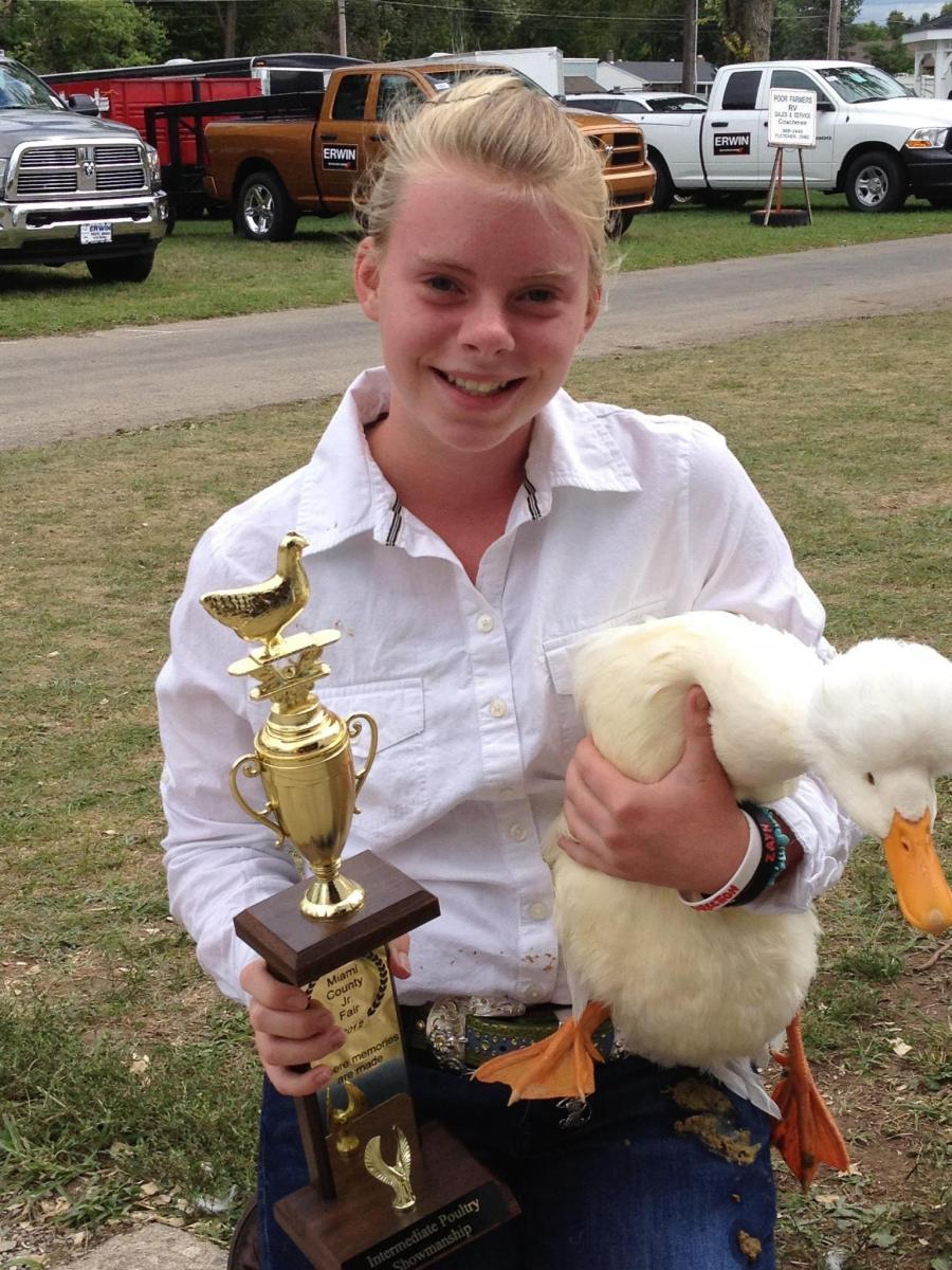 Emma holding a duck and trophy.