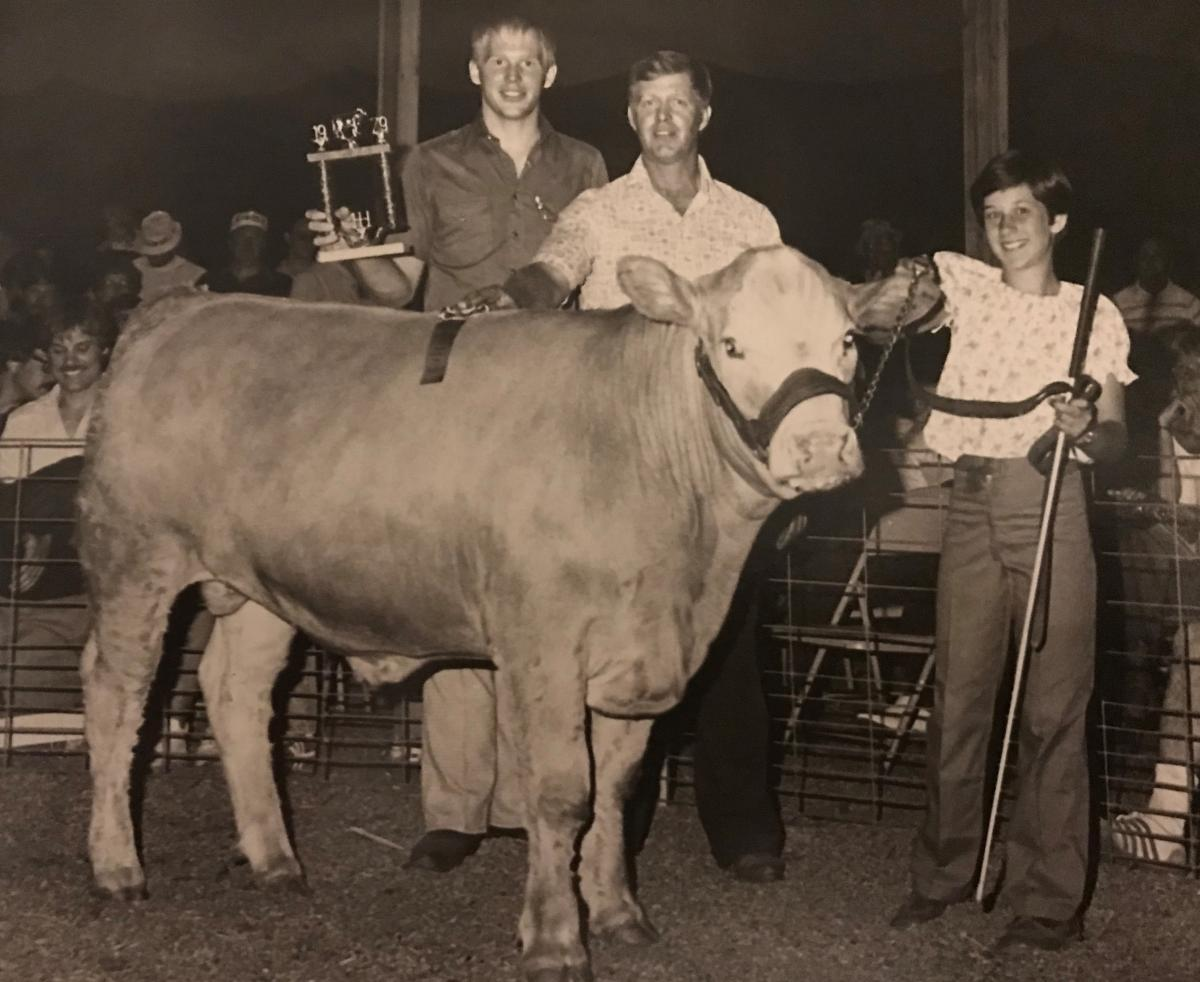 A teenage girl holding the halter of a steer. There are two teenage boys standing behind the steer, one is holding a trophy.