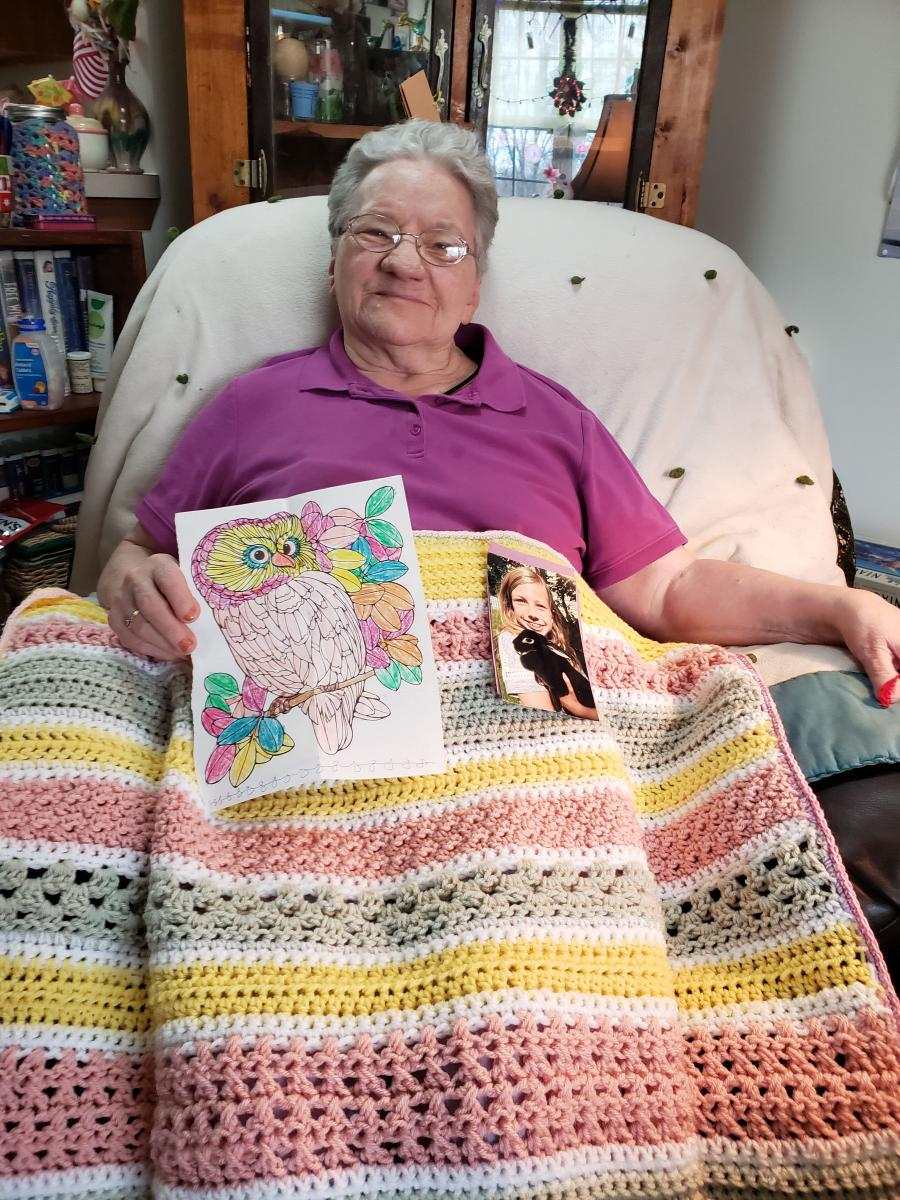 Jean Straley sitting in a chair, holding a photo and coloring page from Olivia.