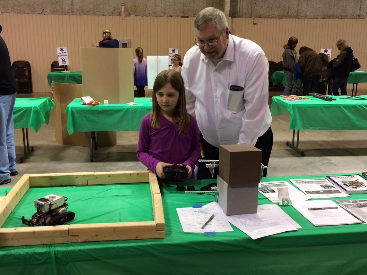 John Smith assisting a 4-H member with their robotics project.