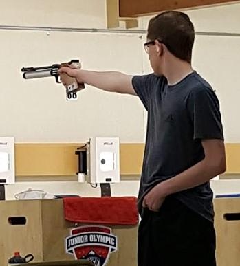 Johnathan aiming an air pistol.