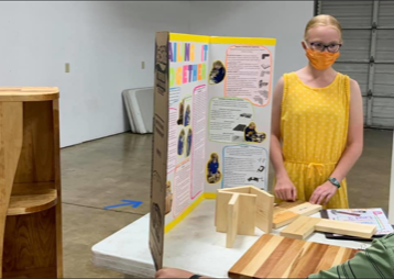 Madelyn having her woodworking project judged.