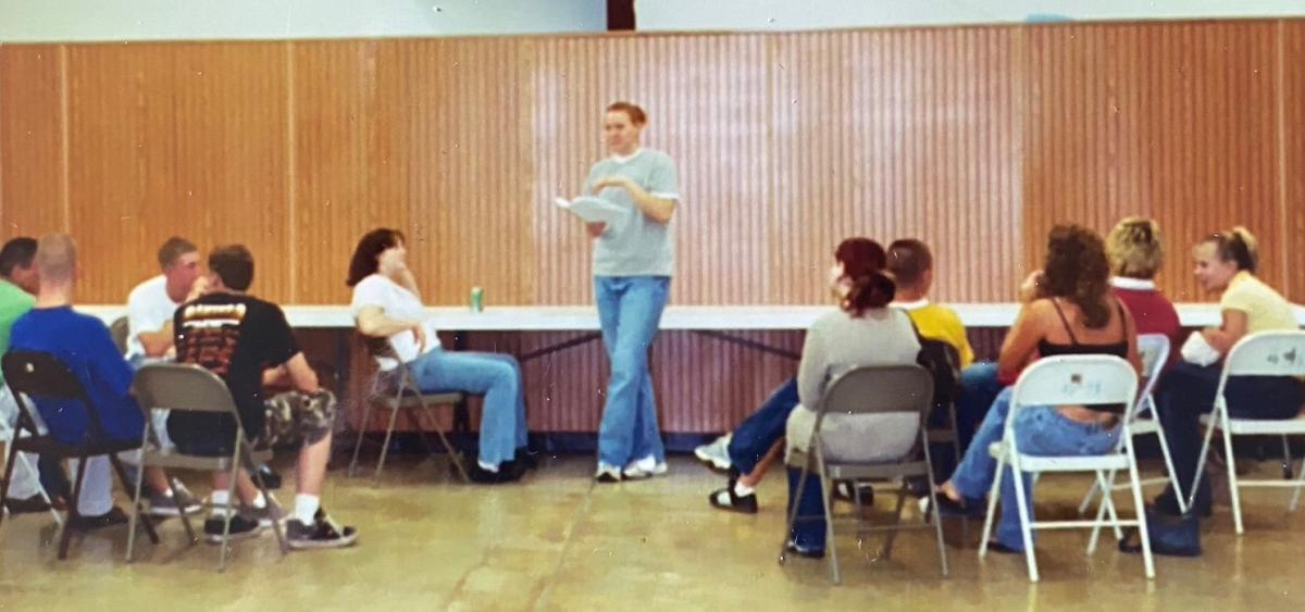 A teenage girl presenting to a small group of people.
