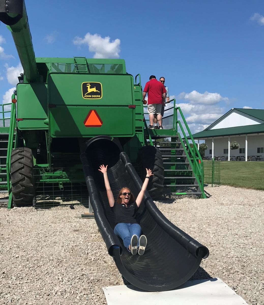 A woman going down a combine slide.