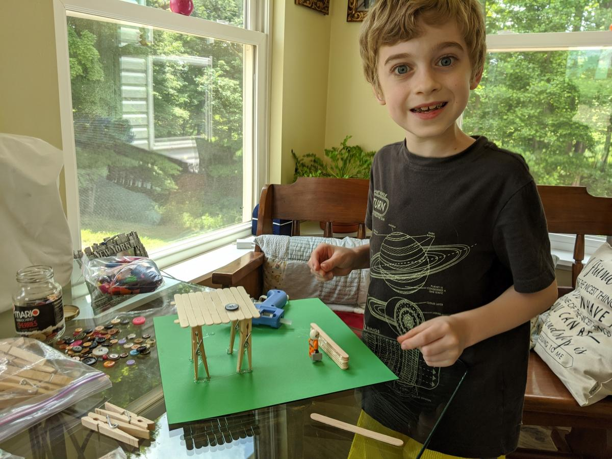 Young boy making a craft using Popsicle sticks.