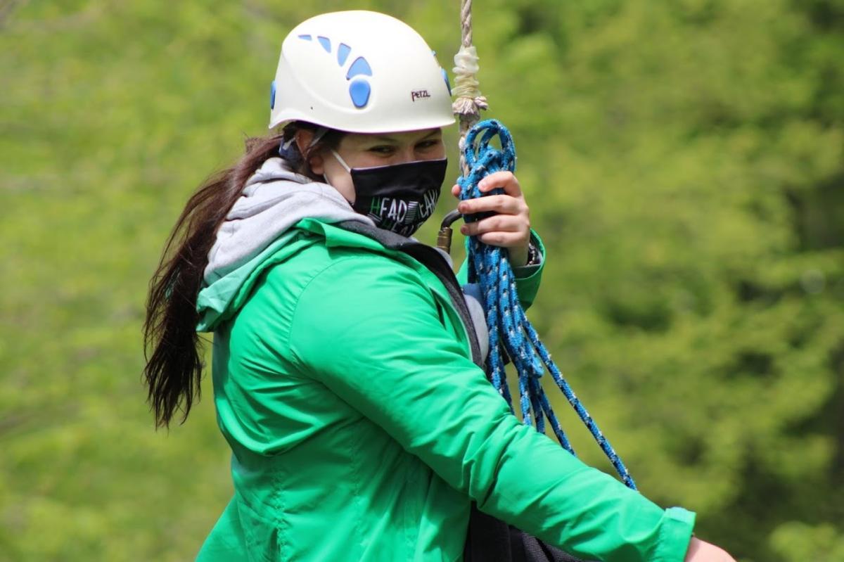 A girl wearing a green jacket ziplining.