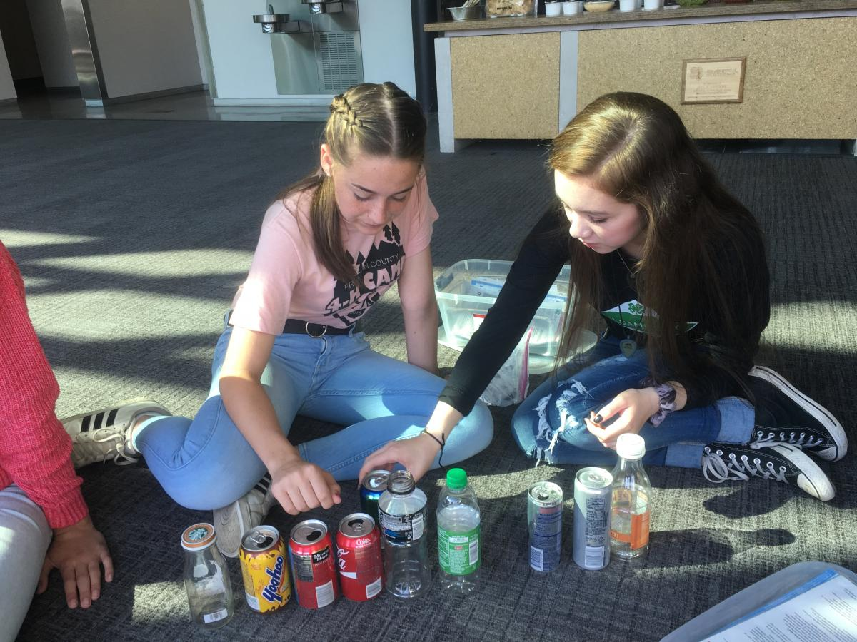 Piper Brill (left) and Alexia Pennington, both from Franklin County, examine beverage containers as they prepare to practice teaching others during the Health Heroes training in September.