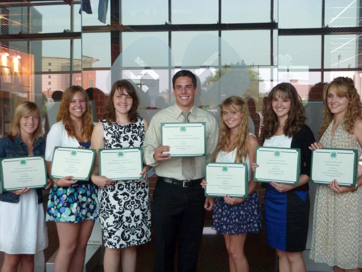 Seven teenagers holding certificates at an awards presentation.