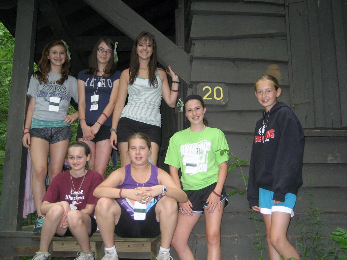Heather with a group of campers in front of a cabin at Tar Hollow.