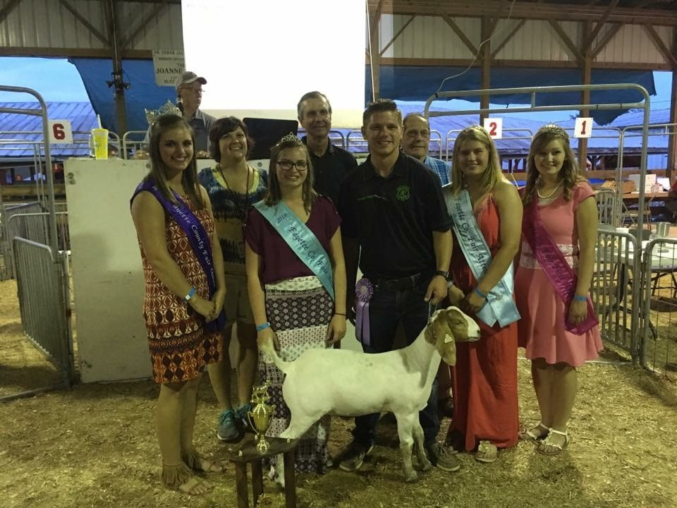Kameron with a goat and group of fair royalty.