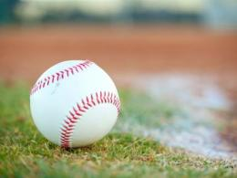 white baseball with red stitching on green grass