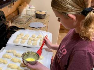 A girl brushing egg wash on dinner rolls.