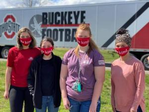 Four college-age girls standing in front of the Ohio State Football semi.