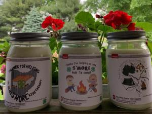 3 candles sitting next to each other featuring labels designed by 4-H youth. There are red flowers around the candles as well as ferns.