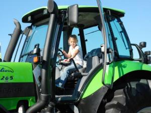 A girl sitting in a tractor cab.