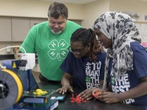 A man helping two teen girls with a coding project.