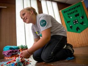 A female 4-H member working on a tie blanket.