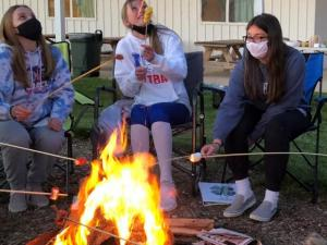 3 girls sitting around a fire roasting marshmallows.
