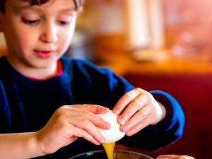Young boy cracking an egg into a mixing bowl.