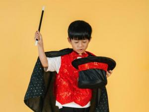 Asian boy in a magicians costume.