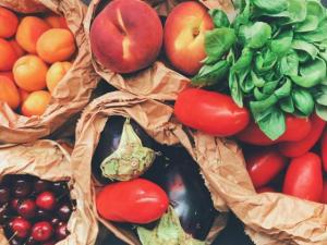 Bags of peaches, spinach, tomatoes, eggplants, oranges, and cherries.