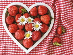 Strawberries in a heart-shaped bowl.