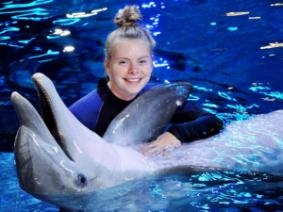 Emma working with a dolphin.
