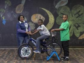 Three black kids with a stationary bike. A chalk mural with a 4-H clover, moon, and other drawings is behind them.