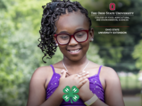 Young girl with hands over her heart and the 4-H clover.