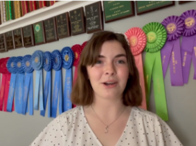 A teenage girl in front of plaques and ribbons.