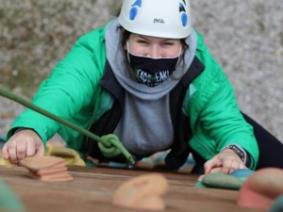 A young woman climbing a rock wall, looking up at the camera.