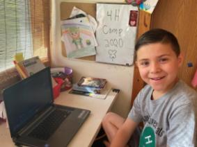 Young boy sitting at the computer for Camp...ish activities. He has made a camp sign to hang on his wall.